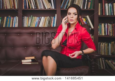 Attractive Business Woman In A Business Suit Sitting On A Leathe