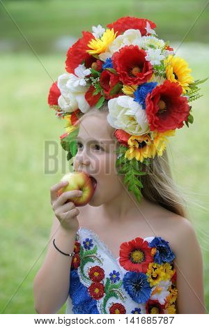 small girl kid with long blonde hair and pretty happy smiling face in prom embriodered white dress and colorful flower national ukrainian wreath crown on head outdoor eating apple