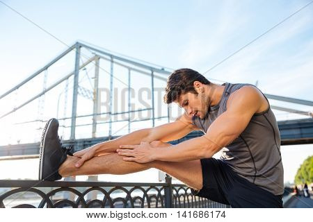 Handsome young sports man doing stretching leaning against bridge railing outdoors