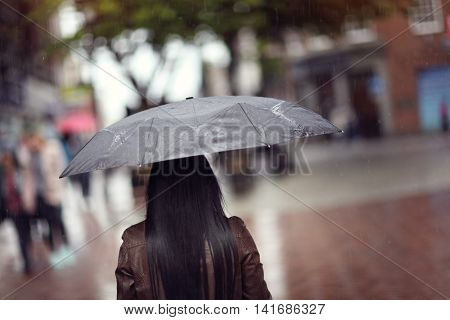 Rain drops falling on a woman holding a black umbrella in a shopping street scene concept for bad weather, winter or protection