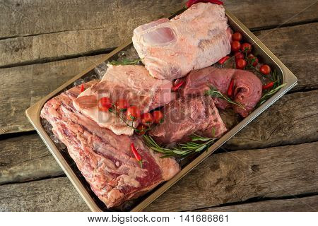 Tray with meat and ice. Tomatoes and rosemary. Pork and beef. Source of amino acids.