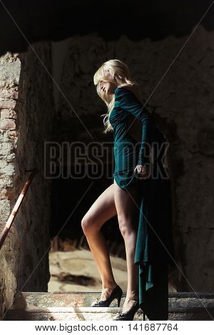 Pretty woman with sensual blonde model in sexy green dress with gorgeous body and long legs in black high-heeled shoes posing on stone stairs