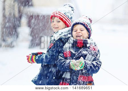 Two little kid boys in colorful clothes, outdoors during snowfall. Active outoors leisure with children in winter on cold snowy days. Happy friends having fun with snow