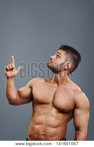 healthy athletic young man with muscles pointing finger up isolated on grey background. Vertical portrait of strong bodybuilder with perfect torso pointing to copyspace above head