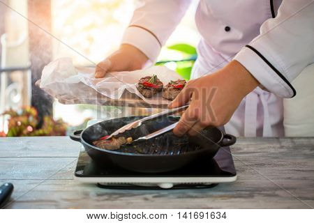 Tongs holding piece of meat. Male hand holds wooden board. Fried beef with chili pepper. Restaurant chef prepares medallions.