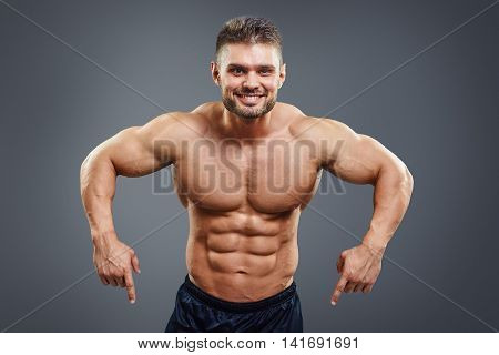 Smiling muscular man pointing down. Half body studio shot isolated on grey