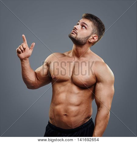 Portrait of muscular man who is pointing a finger up. Fitness athlete showing with hand to the top isolated on gray background