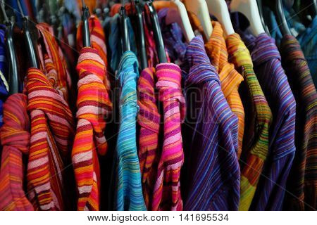 Colorful shirts hanged in a rack for sale in a market