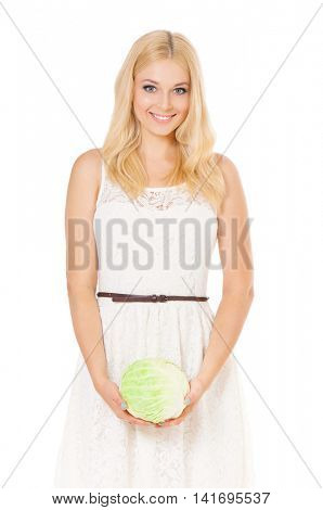 Half-length portrait of beautiful woman holding fresh cabbage and looking at us. Smiling young housewife with green head of cabbage. Studio shot isolated on white background. Healthy eating concept.