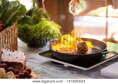 Flame in frying pan. Hand holds bottle over pan. Skilled chef makes a steak. Preparation of beef.