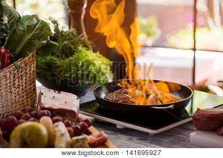Flames in frying pan. Piece of meat being fried. Proven recipe of flambe steak. Asparagus wrapped in bacon strips.
