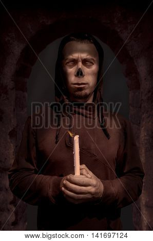 Zombie monk holding candle on gothic door background. Halloween concept. Gothic concept. Horror concept.