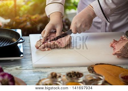 Knife cuts raw meat. Chef's hands in white gloves. What to prepare from pork. Cook will demonstrate skills.