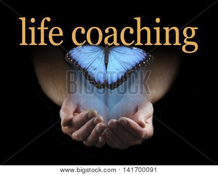 The light touch of a life coach - male hands cupped emerging from a black background with a large blue butterfly rising up towards the words LIFE COACHING