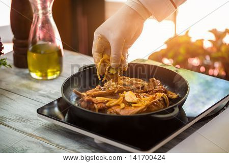 Meat on black frying pan. Hand holds pieces of onion. Chef of cafe prepares pork. Fry until crisp.