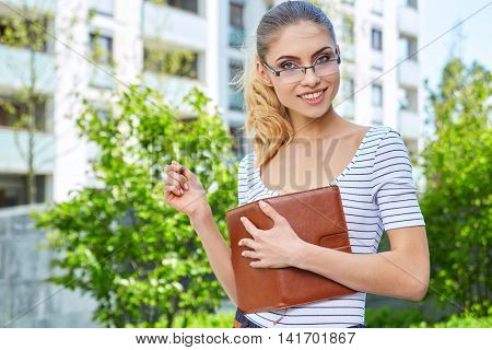 Female student outdoors holding a book and smiling