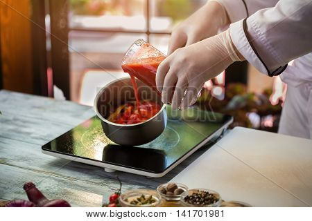 Red liquid pours into saucepan. Hand in glove holds jug. Fresh tomato juice. Restaurant chef makes tasty sauce.