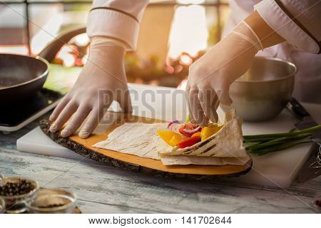 Hand touches pieces of vegetables. Pita bread on wooden board. Dish of organic ingredients. Chef prepares healthy breakfast.