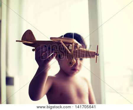 Happy kid playing with toy airplane at home window