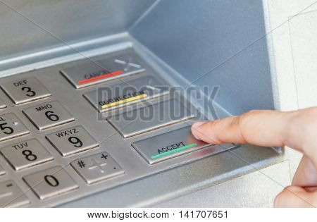 Woman holding the phone with mobile wallet and credit card on the screen against the background of the ATMCloseup of woman hands using smart phone while typing on ATM Slective focus.