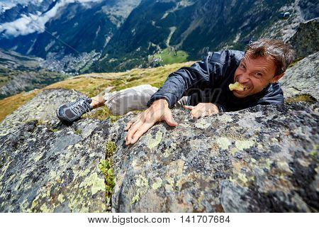 man climbs on a big stone, against a blue sky and valley with Zermatt town. man jokes, shows tension and holding an apple in his mouth