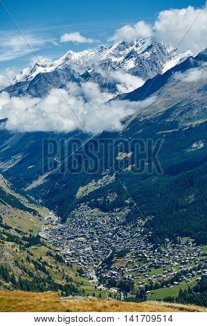 Snow capped alpine mountains and valley with Zermatt town. Trek near Matterhorn mount.