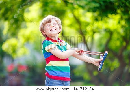 Funny little kid boy shooting wooden slingshot against green tree background. Child having fun in summer.