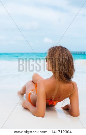 Slender young  woman with long blond hair sitting on the white sand of a tropical beach near the blue ocean,wearing a bikini is orange,wears blue sun glasses,looking in the direction of the ocean,rear view