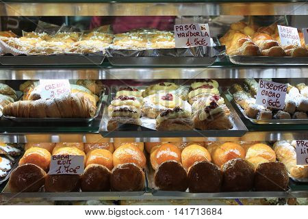 Cakes in showcase. Italian pastry shop with different baba, donuts, jelly, ice cream, cakes with fruits and berries.