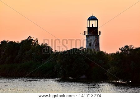 Abandoned old and weathered lighthouse at sunet on a river