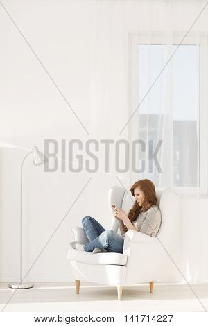 Young red-haired teenager sitting on a white armchair in a bright empty space using her mobile phone