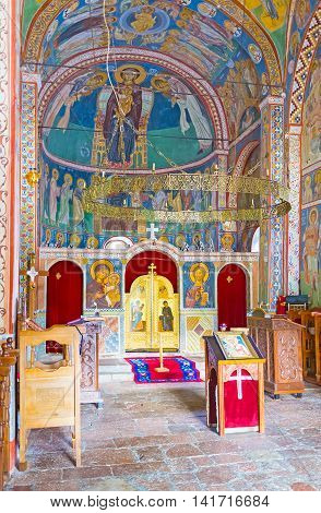 BUDVA MONTENEGRO - JULY 16 2014: The interior of the Assumption Church of Podmaine Monastery decorated by frescos and wooden iconostasis on July 16 in Budva.