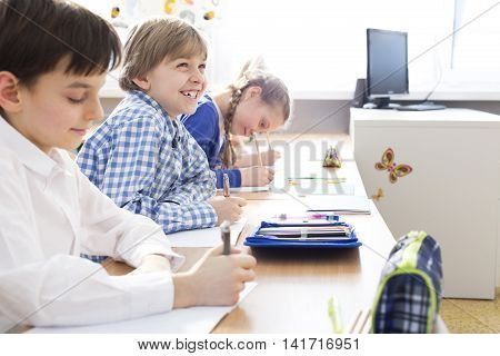 Three children concentrated on making notes during the lesson