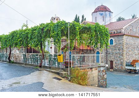 The shady terrace of the cozy outdoor cafe with the grape vines and the Church of Panayia of Agros on the background Cyprus.