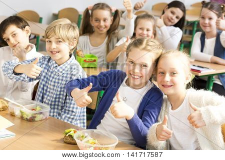 Classroom full of smiled pupils eating pocked lunch with their thumbs up