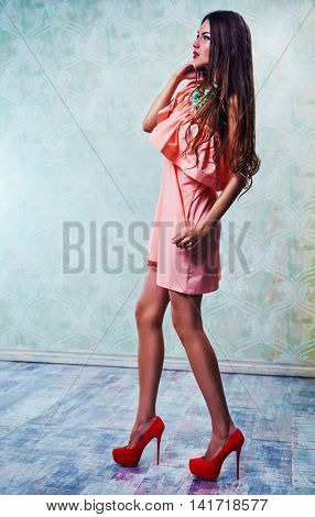 Young slim sexy fashion woman in long pink dress standing on wall background
