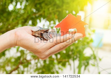 House On A Pile Of Money,hand Holding House With Coins On White Background,finance Concept,business