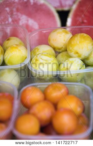 close up of apricots and melons at fruit stand