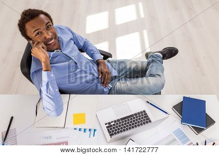 Young man sitting at his armchair with folded leg in office talking on cell phone and smiling to camera. Concept of work and business promotion