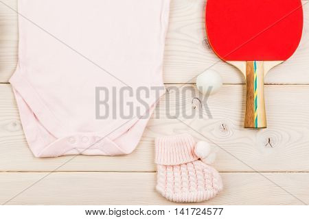 Future occupation concept. Closeup of pink baby girl outfit and table tennis equipment on light wooden surface. Mock up