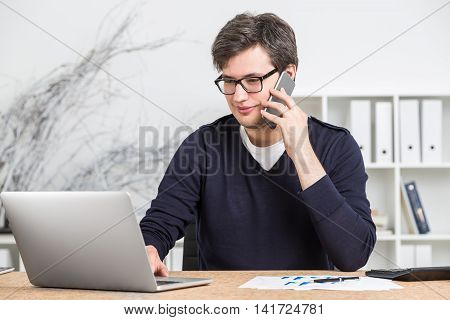 Young man in glasses working on computer and talking on his mobile phone. Concept of work in office. Online sales.