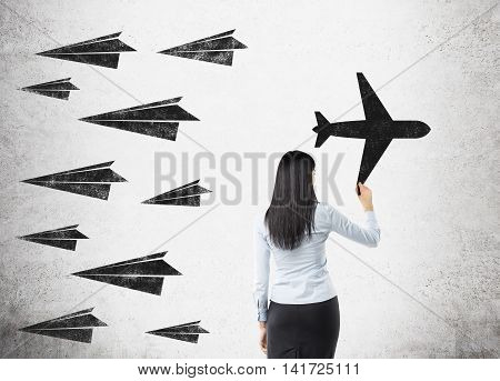 Woman with black hair in formal suit is drawing airplane on concrete wall. Sketches of other planes on it. They fly different direction. Concept of original idea.