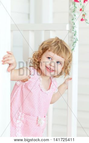 Little cute girl in a pink dress looks into the street and smiling from behind the white door on the porch. Provence style