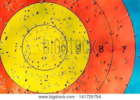 Centre of archery target with arrow holes. Gold red and blue middle of competition target marked where arrows have penetrated including bullseye