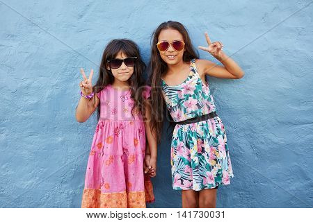Portrait of two little girls standing together wearing sunglasses gesturing peace sign against blue wall. Stylish preteen girls posing to the camera with victory hand sign.