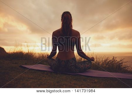 Fitness Woman In Lotus Yoga Pose During Sunset