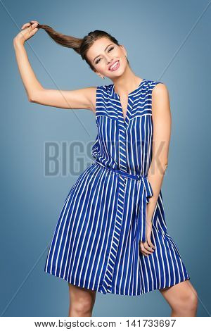 Pretty young woman posing in casual summer dress at studio. Beauty, fashion.