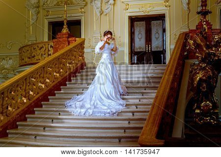 a beautiful lady in a long white dress is going upstairs in the theatre