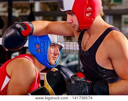 Two sport men boxer wearing boxer helmet and boxer gloves boxing sport .