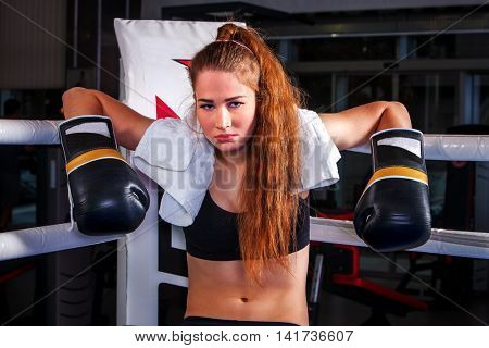 Sport boxing girl wearing black boxing gloves sitting in corner of boxing ring.
